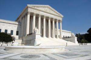"The front of the US Supreme Court in Washington, DC. Completed in 1935, the US Supreme Court building in Washington, DC, is the first to have been built specifically for the purpose, inspiring Chief Justice Charles Evans Hughes to remark, ""The Republic endures and this is the symbol of its faith."" The Court was established in 1789 and initially met in New York City. When the national capital moved to Philadelphia, the Court moved with it, before moving to the permanent capital of Washington, DC, in 1800. Congress lent the Court space in the new Capitol building, and it was to change its meeting place several more times over the next century, even convening for a short period in a private house after the British set fire to the Capitol during the War of 1812. The classical Corinthian architectural style was chosen to harmonize with nearby congressional buildings, and the scale of the massive marble building reflects the significance and dignity of the judiciary as a co-equal, independent branch of government. The main entrance is on the west side, facing the Capitol. On either side of the main steps are figures sculpted by James Earle Fraser. On the left is the female Contemplation of Justice. On the right is the male Guardian or Authority of Law. On the architrave above the pediment is the motto ""Equal Justice under Law."" Capping the entrance is a group representing Liberty Enthroned, guarded by Order and Authority, sculpted by Robert Aitken. At the east entrance are marble figures sculpted by Hermon A. MacNeil. They represent great law givers Moses, Confucius, and Solon, flanked by Means of Enforcing the Law, Tempering Justice with Mercy, Settlement of Disputes between States, and Maritime and other functions of the Supreme Court. The architrave carries the motto ""Justice the Guardian of Liberty."" The interior of the building is equally filled with symbolic ornamentation. The main corridor is known as the Great Hall and contains double rows of marble columns and busts of all former chief justices. At its east end, oak doors open into the Court Chamber, where the justices preside. Most of the second floor is devoted to office space. The library occupies the third floor and has a collection of more than 450,000 volumes.  The Supreme Court consists of the Chief Justice of the United States and eight Associate Justices. The term of the Court begins on the first Monday in October and lasts for the full year. Approximately 8,000 petitions are filed with the Court each term. A further 1,200 applications of various kinds are filed that can be acted upon by a single justice.  The Supreme Court has appellate jurisdiction except ""in all Cases affecting Ambassadors, other public ministers and Consuls, and those in which a State shall be Party"" (Constitution, art. III, §2), for which it has original jurisdiction. Congress has also from time to time conferred on the Supreme Court the power to prescribe rules of procedure to be followed by the lower courts."